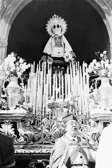 El Jueves Santo de 1960, el Capellán de la cofradía bendice la nueva Imagen de María Stma. de la Caridad a la salida de San Isidoro junto al nuevo trono que la acompaña, todo obra de Francisco Palma Burgos.